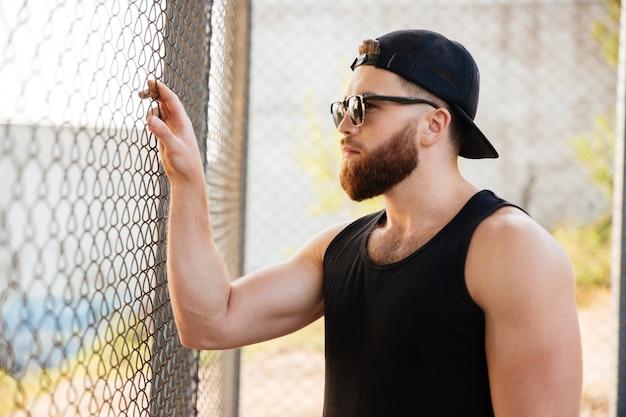 Bliska portret młodego brodatego mężczyzny patrząc przez metalowe ogrodzenie miejskie w okularach przeciwsłonecznych i czapce na zewnątrz