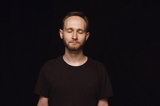 Bliska portret młodego człowieka na białym tle. model męski z zamkniętymi oczami. rozważny. wyraz twarzy, ludzka natura i koncepcja emocji.
