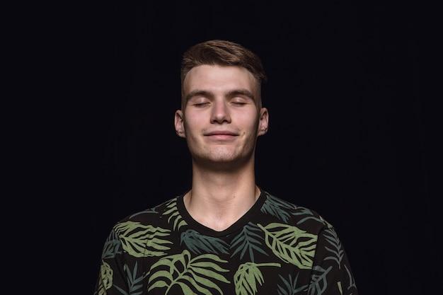 Bliska portret młodego człowieka na białym tle na czarnej przestrzeni. myślenie i uśmiechanie się