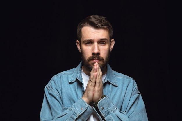 Bliska portret młodego człowieka na białym tle na czarnej ścianie. zdjęcie prawdziwych emocji męskiego modelu. modląc się i płacz, wygląda na smutnego i pełnego nadziei. wyraz twarzy, koncepcja ludzkich emocji.