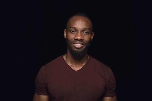 Bliska portret młodego człowieka na białym tle na czarnym studio