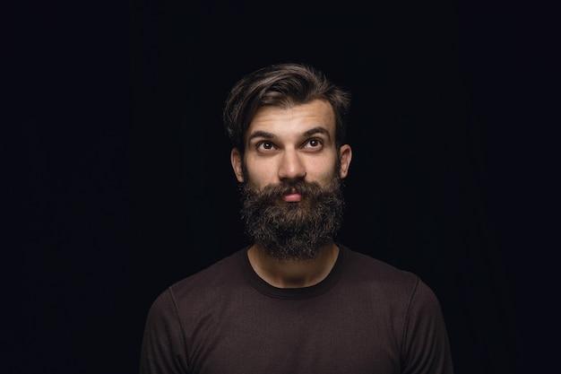 Bliska portret młodego człowieka na białym tle na tle czarnego studia. zdjęcia prawdziwych emocji modela. śniący i uśmiechnięty, pełen nadziei i szczęśliwy. wyraz twarzy, koncepcja ludzkich emocji.