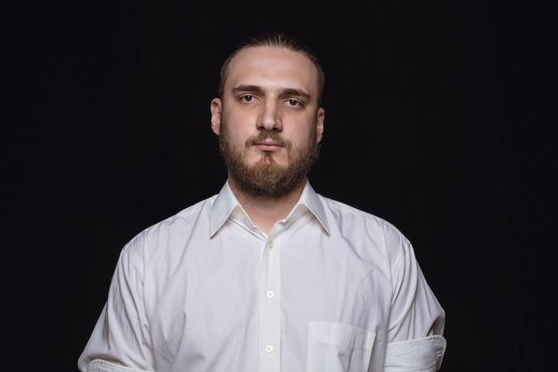 Bliska portret młodego człowieka na białym tle na tle czarnego studia