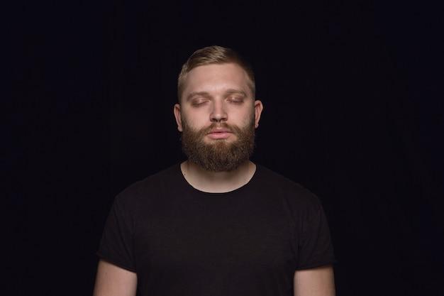 Bliska portret młodego człowieka na czarnym studio