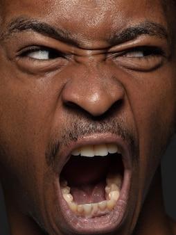 Bliska portret młodego i emocjonalnego człowieka afroamerykańskiego. bardzo szczegółowa sesja zdjęciowa modela z zadbaną skórą i jasnym wyrazem twarzy. pojęcie ludzkich emocji.