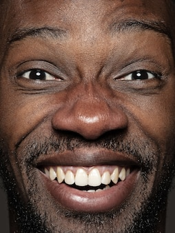 Bliska portret młodego i emocjonalnego człowieka afroamerykańskiego. model męski o zadbanej skórze i jasnym wyrazie twarzy. pojęcie ludzkich emocji. szczęśliwy uśmiechnięty.