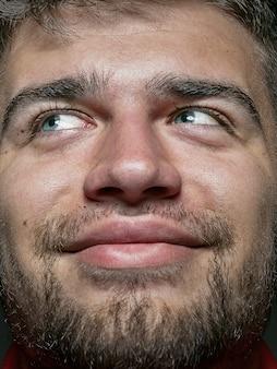 Bliska portret młodego i emocjonalnego kaukaski mężczyzna. bardzo szczegółowe zdjęcie modela z zadbaną skórą i jasnym wyrazem twarzy. pojęcie ludzkich emocji. uśmiecha się i wygląda na szczęśliwego.