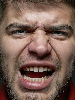 Bliska portret młodego i emocjonalnego kaukaski mężczyzna. bardzo szczegółowe zdjęcie modela z zadbaną skórą i jasnym wyrazem twarzy. pojęcie ludzkich emocji. wściekły krzyk.