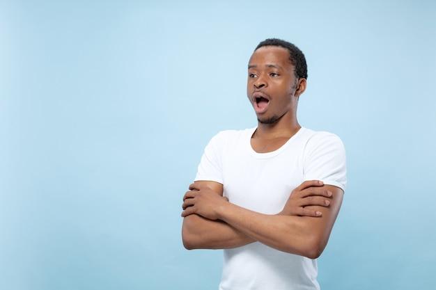 Bliska portret młodego mężczyzny afro-amerykańskiego w białej koszuli. stojące ręce skrzyżowane, zszokowane i zdumione.