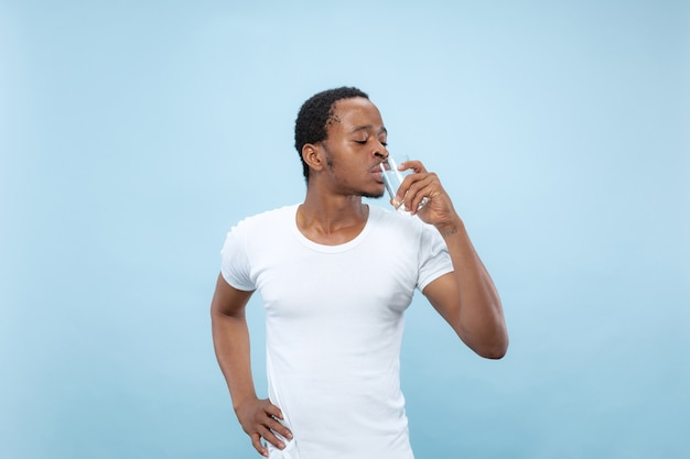 Bliska portret młodego mężczyzny afro-amerykańskiego w białej koszuli. trzyma szklankę i wodę pitną.
