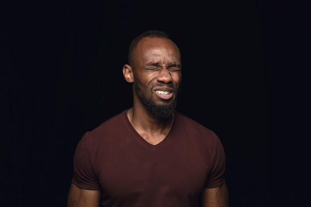 Bliska portret młodego mężczyzny afrykańskiego na czarnym studio