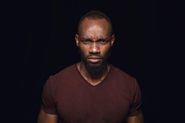 Bliska portret młodego mężczyzny afrykańskiego na czarnym tle