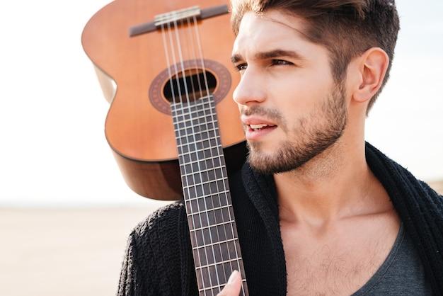 Bliska portret młodego mężczyzny dorywczo z gitarą na ramieniu na plaży