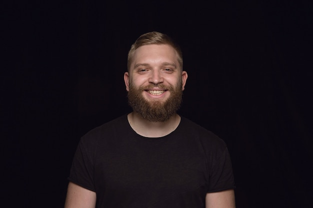 Bliska portret młodego mężczyzny na białym tle na czarnej ścianie. sfotografowanie prawdziwych emocji modela. uśmiechnięty, szczęśliwy. wyraz twarzy, czysta i wyraźna koncepcja ludzkich emocji.
