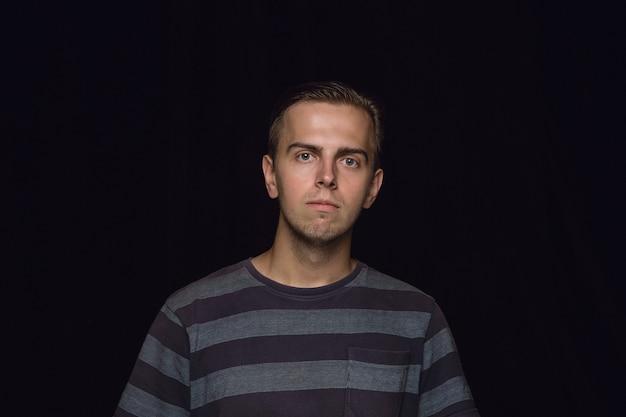 Bliska portret młodego mężczyzny na białym tle na czarnej ścianie