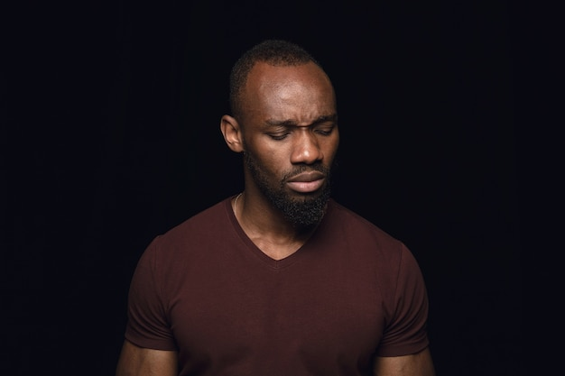 Bliska portret młodego mężczyzny na białym tle na ścianie czarnego studia
