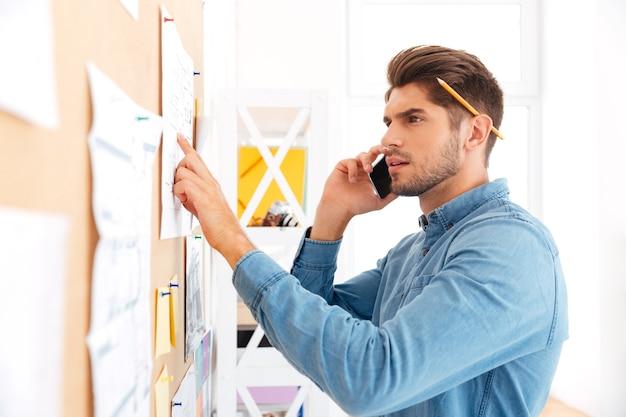 Bliska portret młodego skoncentrowanego biznesmena dorywczo rozmawiającego przez telefon i wskazującego na tablicę