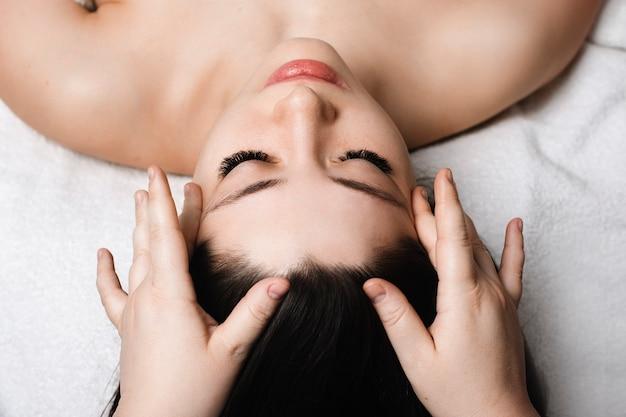 Bliska portret młodej atrakcyjnej kobiety o masaż twarzy do pielęgnacji skóry przez kosmetologa w centrum odnowy biologicznej.