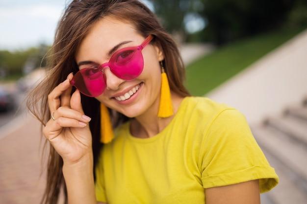 Bliska portret młodej atrakcyjnej uśmiechniętej kobiety bawiącej się w parku miejskim, pozytywna, szczęśliwa, ubrana w żółty top, kolczyki, różowe okulary przeciwsłoneczne, trend w modzie lato, stylowe akcesoria, kolorowe