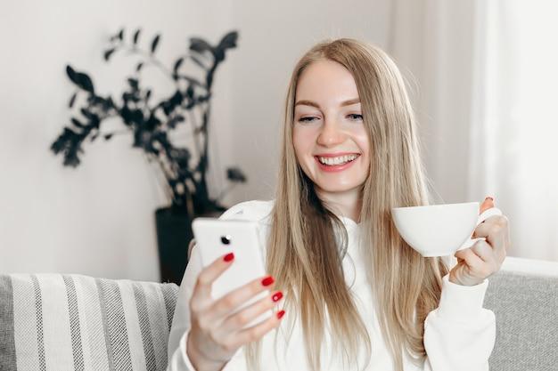 Bliska portret młodej blond studentki wideo, dzwoniąc przez telefon podczas kwarantanny w domu