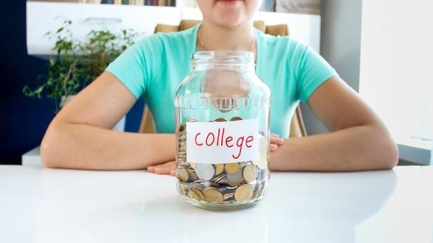 Bliska portret młodej damy w koszulce siedzącej przy białym stole, na którym znajduje się, pełen monet, słoik z napisem kredyt