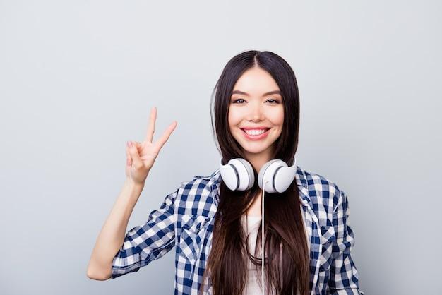 Bliska portret młodej dziewczyny w przypadkowy wygląd z zestawem słuchawkowym co znak pokoju