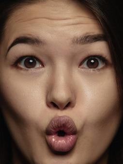 Bliska portret młodej i emocjonalnej chinki. bardzo szczegółowa sesja zdjęciowa modelki o zadbanej skórze i jasnym wyrazie twarzy. pojęcie ludzkich emocji. zdziwiony, zdumiony.