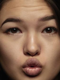 Bliska portret młodej i emocjonalnej chinki. bardzo szczegółowe zdjęcie modelki o zadbanej skórze i jasnym wyrazie twarzy. pojęcie ludzkich emocji. wysyłanie buziaków.