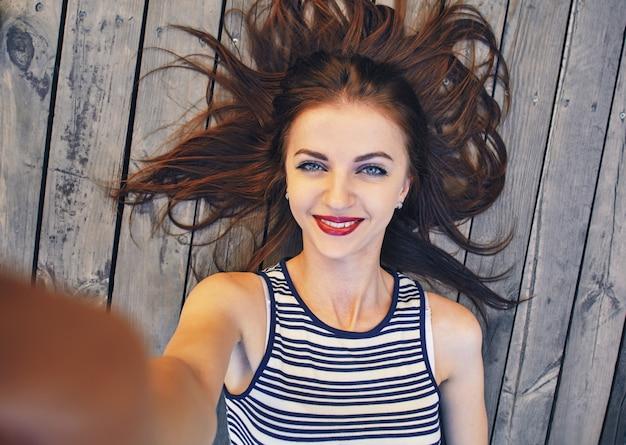 Bliska portret młodej kobiety atrakcyjne, trzymając aparat cyfrowy smartphone z rękami i biorąc autoportret siebie podczas pracy w sieci. podróże i technologia na świeżym powietrzu.