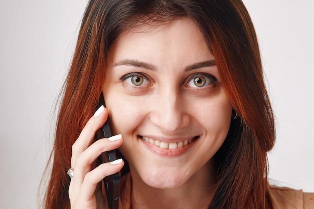 Bliska portret młodej kobiety brunetka rozmawia jej telefon komórkowy