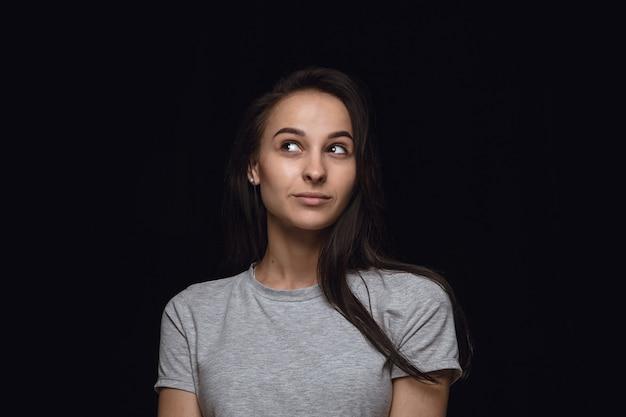 Bliska portret młodej kobiety na białym tle na tle czarnego studia. sfotografowanie prawdziwych emocji modelki. śniący i uśmiechnięty, pełen nadziei i szczęśliwy. wyraz twarzy, koncepcja ludzkich emocji.