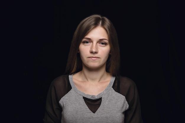 Bliska portret młodej kobiety na białym tle na tle czarnego studia