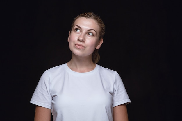 Bliska portret młodej kobiety na białym tle na tle czarnego studia.