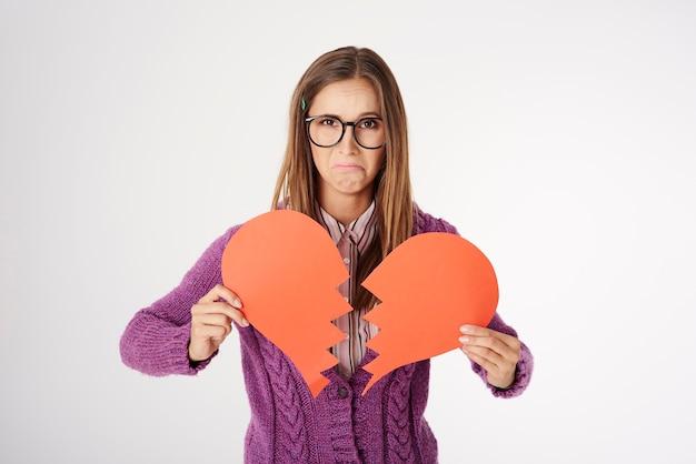 Bliska portret młodej kobiety posiadającej kształt złamanego serca