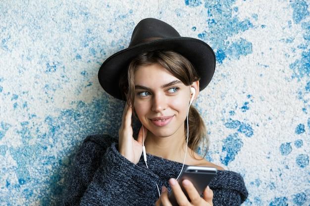 Bliska portret młodej kobiety ubranej w sweter i kapelusz na niebieskiej ścianie, słuchając muzyki przez słuchawki, trzymając telefon komórkowy, odwracając wzrok