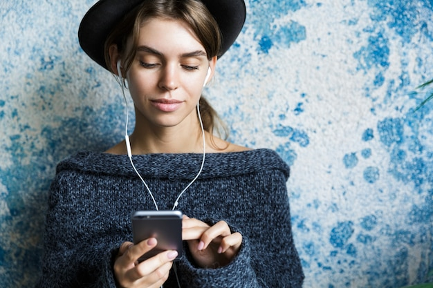 Bliska portret młodej kobiety ubranej w sweter i kapelusz na niebieskiej ścianie, słuchanie muzyki przez słuchawki, trzymając telefon komórkowy