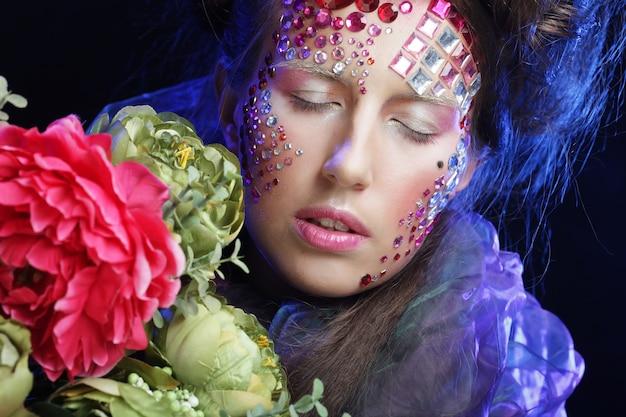 Bliska portret młodej kobiety w twórczy obraz z dużymi kwiatami.