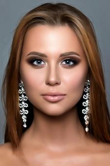 Bliska portret młodej kobiety z brązowymi smokey eyes na sobie długie kolczyki. nowoczesny makijaż ślubny. idealne brwi.