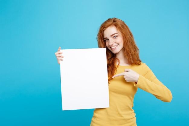 Bliska portret młodej pięknej atrakcyjnej rude włosy imbir uśmiechnięta dziewczyna pokazuje pusty znak niebieski pastelowe ściany kopia przestrzeń