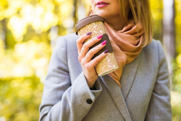 Bliska portret młodej pięknej kobiety w szarym płaszczu z kawą