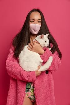 Bliska portret młodej pięknej kobiety z maską ochronną trzyma kota na białym tle