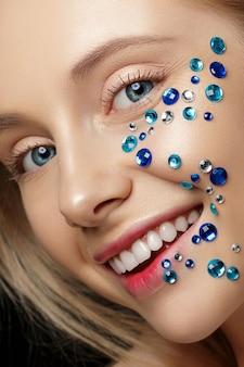 Bliska portret młodej pięknej kobiety z niebieskimi kryształkami jej twarz