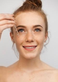 Bliska portret młodej pięknej rudowłosej kobiety stosującej kwas hialuronowy z uśmiechem zakraplaczem na białym tle na białej ścianie.