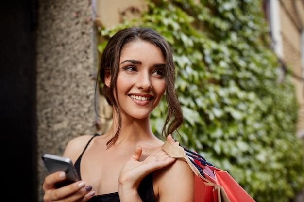 Bliska portret młodej przystojnej wesołej ciemnowłosej dziewczyny kaukaskiej, patrząc na bok z radosnym i zrelaksowanym wyrazem twarzy, gawędząc z przyjaciółmi przez telefon, niosąc torby na zakupy do domu po zakupie ne