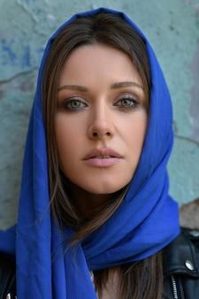 Bliska portret młodej religijnej brunetki włosy zielone delikatne oczy piękna twarz dorosłej kobiety lub młodej dziewczyny z niebieskim jedwabnym szalikiem pokrytym głową w czarnej skórzanej kurtce na tle starego ceglanego muru