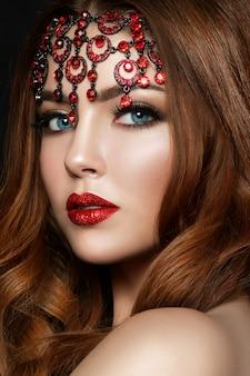 Bliska portret młodej rudowłosej kobiety na sobie czerwone usta z błyszczy i brązowe oczy smokey. makijaż nowoczesnej mody.