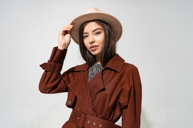 Bliska portret moda kryty studio wspaniałej kobiety w stylowy zimowy brązowy płaszcz i czarny kapelusz