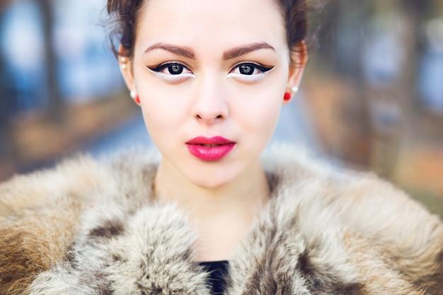 Bliska portret moda na zewnątrz pięknej azjatyckiej dziewczyny z idealną skórą na sobie futrzaną kurtkę, jasny makijaż w stylu pin up i soczewki oczu. portret na zewnątrz upadku.