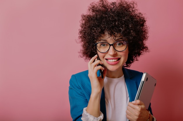 Bliska portret modnej stylowej kobiety biznesu z krótką fryzurą afro w okularach i rozmawia na smartfonie