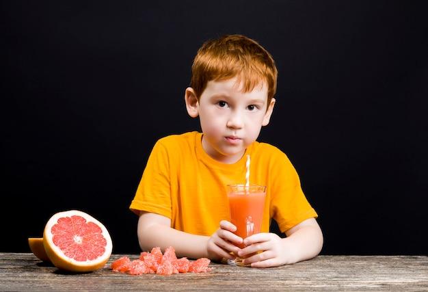 Bliska portret na chłopca z sokiem grejpfrutowym